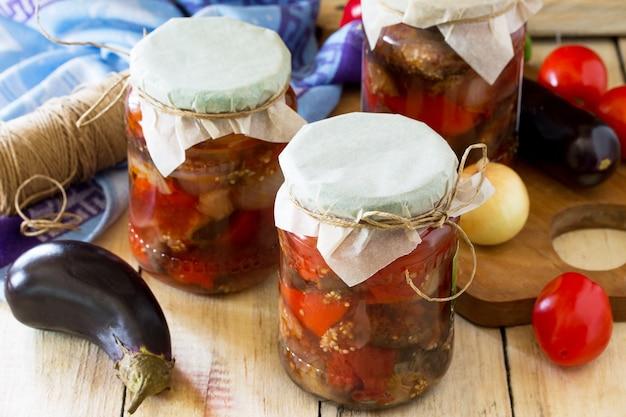 Salada de berinjela com vegetais em conserva caseira no fundo de madeira da cozinha