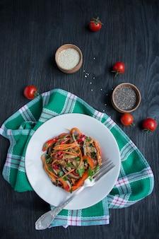 Salada de berinjela, pimenta e cenoura. salada coreana de berinjela. branco. vegetarianismo. vista de cima. . postura plana.