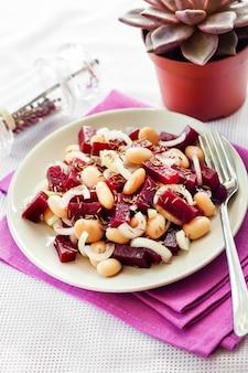 Salada de beterraba com feijão branco, pickles e cebola, temperada com azeite e aromatizada com sementes de cominho