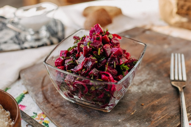 Salada de beterraba em fatias, salgada com verduras dentro de vidro na mesa rústica de madeira marrom