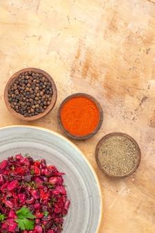 Salada de beterraba em um prato de cerâmica com pimenta preta moída de açafrão-da-índia de beterraba em um fundo de madeira com espaço livre