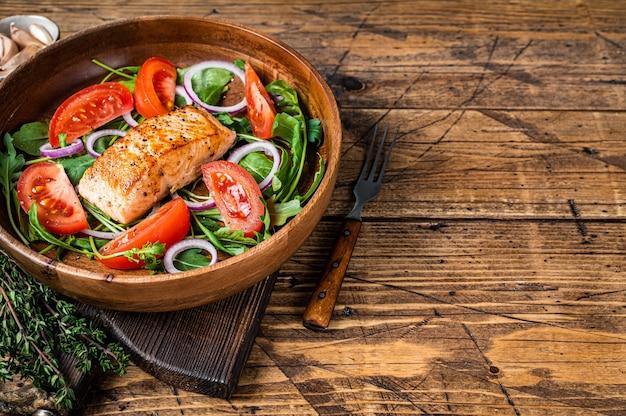 Salada de bife de salmão com folhas verdes de rúcula, abacate e tomate em prato de madeira