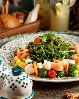 Salada de brocoli com salmão cenoura tomate cereja mozzarellcauliflower arugulhomemade limonada e pão na mesa