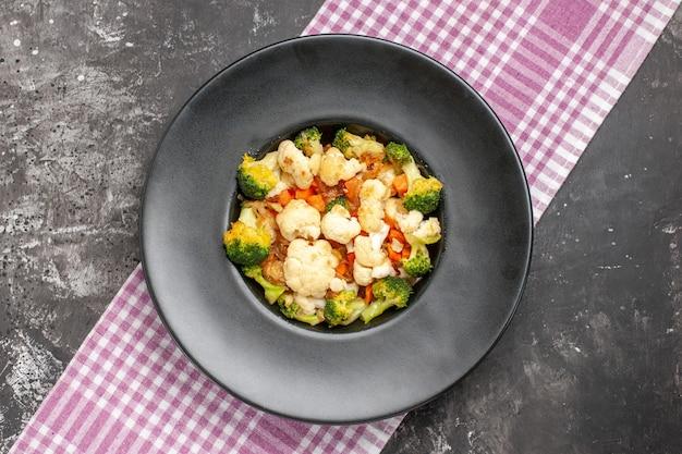 Salada de brócolis e couve-flor vista de cima em prato oval preto toalha de mesa quadriculada rosa e branca em espaço livre de superfície escura