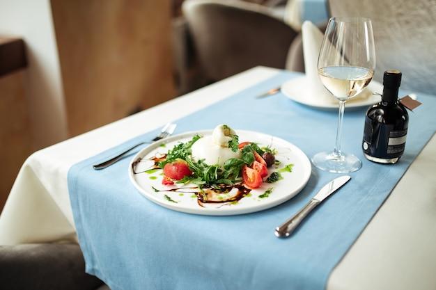 Salada de buratta espanhola com legumes e verduras na mesa do restaurante servido