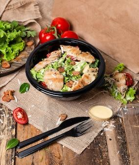 Salada de caesar da galinha com queijo parmesão desbastado, tomate, alface, biscoitos.