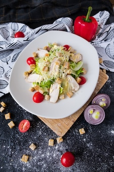 Salada de caesar fresca com galinha em uma placa branca na pedra escura.