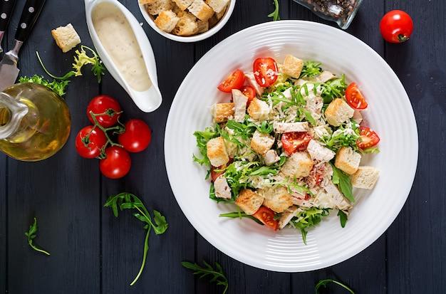 Salada de caesar grelhada saudável da galinha com tomates, queijo e pão torrado.
