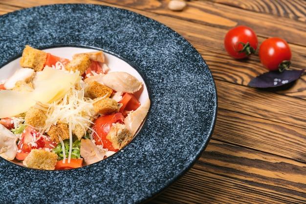 Salada de caesar grelhada saudável do frango com queijo e pão torrado.