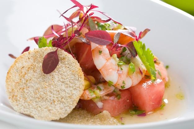 Salada de camarão close-up com melancia, decorada com flores comestíveis.