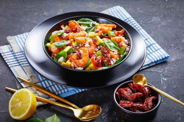 Salada de camarão com abacate e espinafre com tomate seco, pedaços de bacon frito, queijo cotija esfarelado, cebola roxa em uma tigela preta sobre uma mesa de concreto
