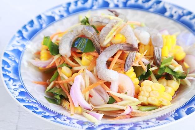 Salada de camarão crua picante comida tailandesa favorita, camarão vegetal e cru com pimenta de água no prato branco, caseiro em restaurante