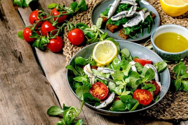 Salada de campo verde com anchovas em conserva ou filé de sardinha e tomate cereja, servido em uma tigela azul com limão e azeite no guardanapo de palha sobre a velha mesa de madeira. Foto Premium