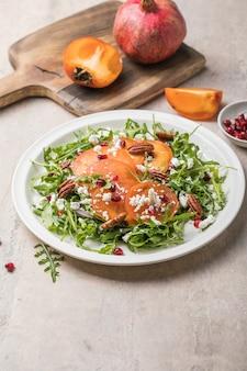 Salada de caqui com rúcula, nozes, queijo de cabra, romã. conceito de comida vegetariana saudável.
