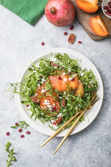 Salada de caqui com rúcula, nozes, queijo de cabra, romã. conceito de salada de comida vegetariana saudável.
