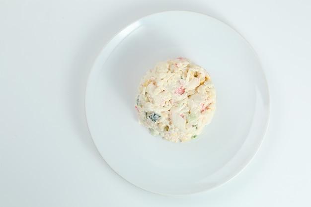 Salada de caranguejo com arroz na chapa branca closeup com espaço de cópia. salada tradicional russa com palitos de caranguejo isolados no branco