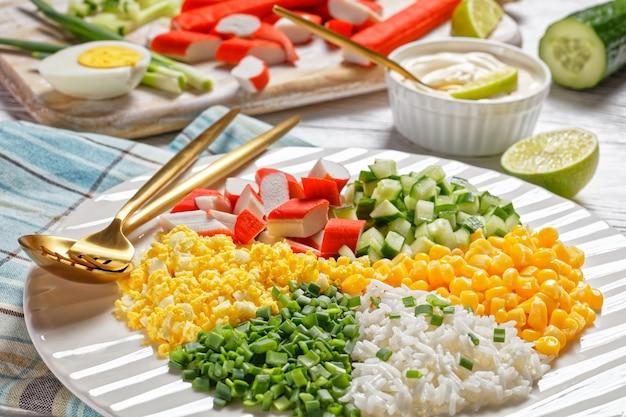 Salada de caranguejo de surimi com milho enlatado, pepino, ovo cozido de cebolinha, arroz de jasmim dividido em setores em um prato branco sobre fundo branco de madeira, vista de cima, close-up