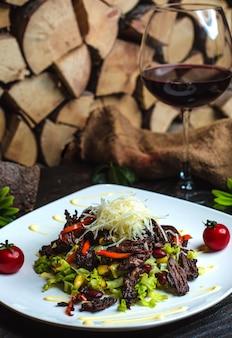 Salada de carne com feijão e um copo de vinho tinto