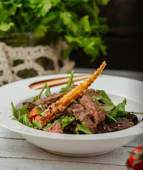 Salada de carne com rúcula, tomate e pão com sementes de gergelim