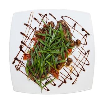 Salada de carne com verduras em um prato em um fundo branco