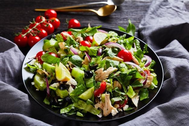Salada de carne de frango, azeitonas, cebola roxa, tomate, pepino, hortelã, alface polvilhada com queijo feta esmigalhado em uma tigela preta, vista panorâmica de cima