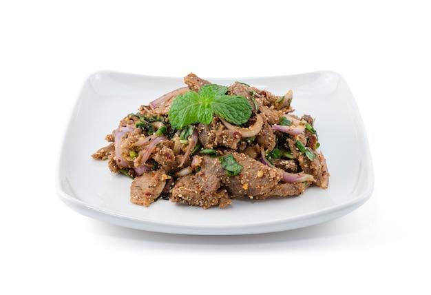 Salada de carne de porco grelhada picante na parede branca.