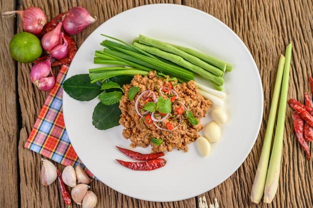 Salada de carne de porco picada picante em um prato branco com lentilhas, folhas de limão kaffir e cebolinhas.