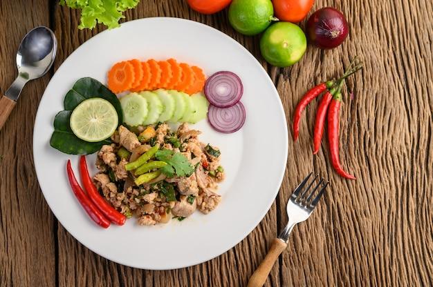 Salada de carne de porco picada picante em um prato branco na mesa de madeira.