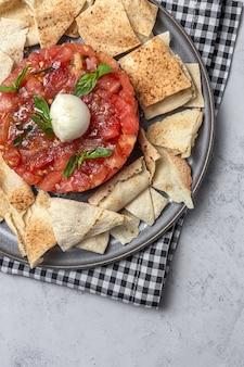 Salada de carpaccio de tomate caseiro com mozzarella, azeite e manjericão com pão árabe. conceito de comida saudável