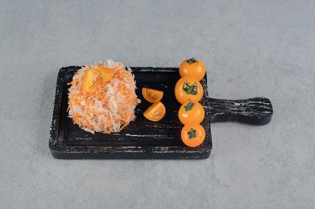 Salada de cenoura de cor laranja com ingredientes mistos e tomate cereja.