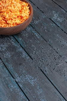Salada de cenoura ralada de frente para dentro do prato em uma mesa rústica azul-escura salada de saúde cor dieta madura
