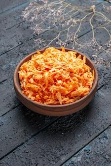 Salada de cenoura ralada de frente para dentro do prato marrom na mesa rústica azul-escura salada de saúde cor de salada de vegetais maduros