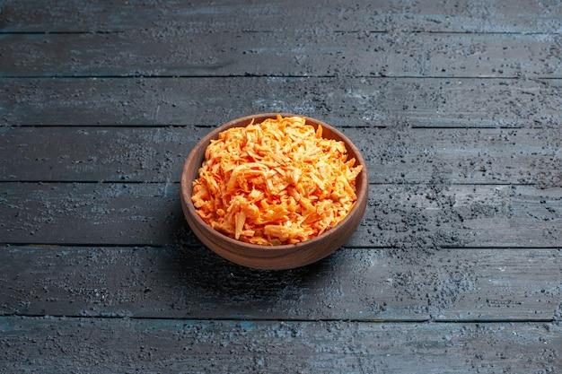 Salada de cenoura ralada de frente para dentro do prato na mesa rústica azul-escura salada cor madura dieta saudável vegetal