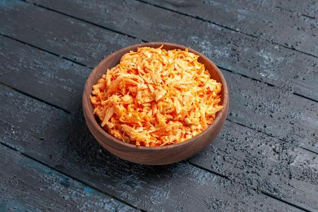Salada de cenoura ralada de frente para dentro do prato na mesa rústica azul-escura salada cor madura dieta saudável