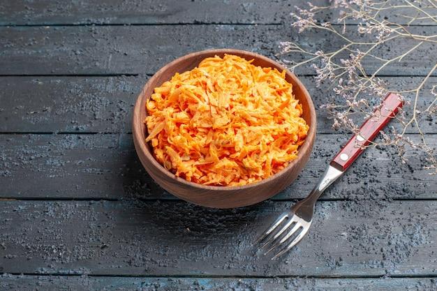 Salada de cenoura ralada em frente a um prato marrom em uma mesa rústica azul-escura salada de saúde cor de vegetais maduros