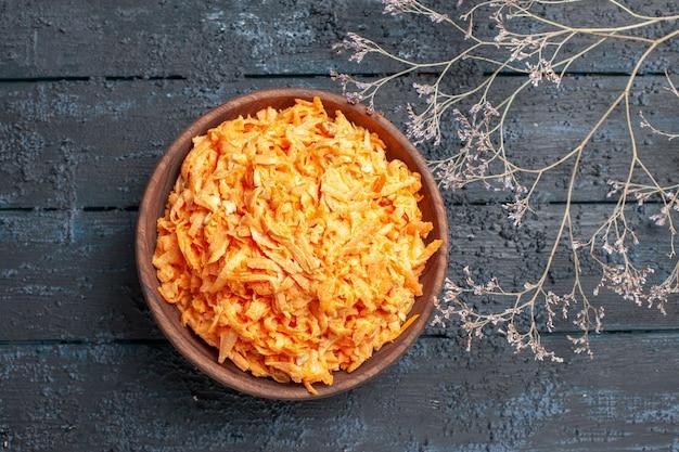 Salada de cenoura ralada vista de cima dentro do prato marrom na mesa rústica azul-escura salada de saúde cor dieta vegetal maduro