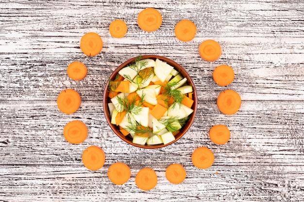 Salada de cenoura, rodeada com fatias de cenoura, vista superior na superfície de madeira