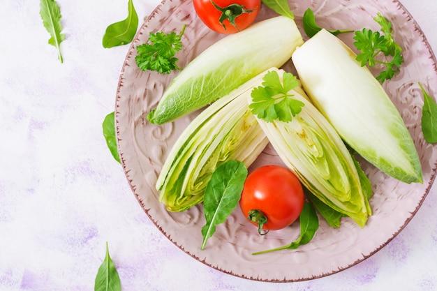 Salada de chicória fresca e saudável (witloof) e tomate em um prato. menu dietético. comida saudável. vista do topo
