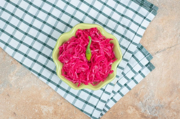 Salada de chucrute vermelho em tigela verde com toalha de mesa