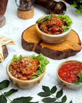 Salada de churrasco em panela de barro em um toco