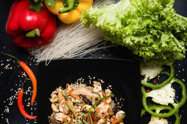 Salada de cogumelos e vegetais num prato em fundo escuro. refeição de cozinha oriental