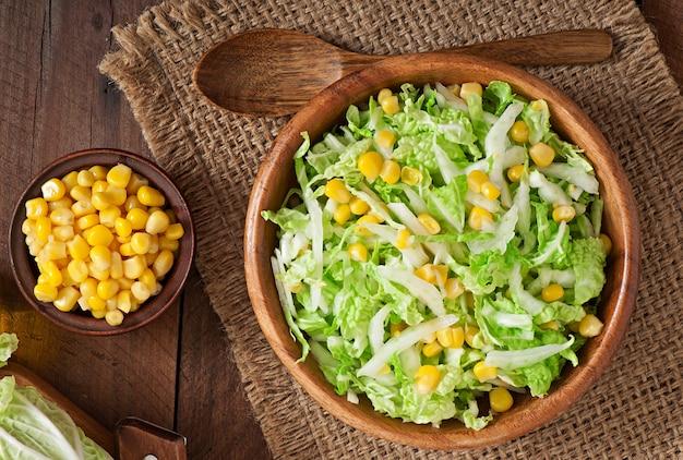 Salada de couve chinesa com milho doce em uma tigela de madeira