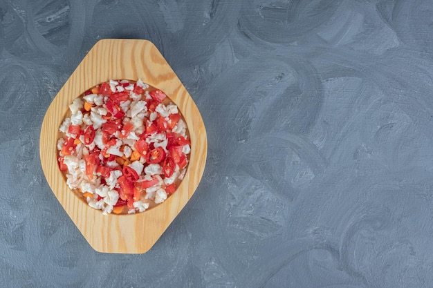 Salada de couve-flor e pimenta em uma travessa de madeira misturada com cenouras em fundo de mármore.