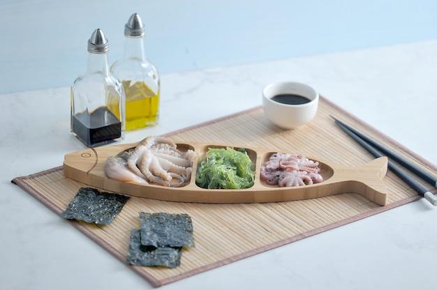 Salada de couve mar couve, polvo em um prato de madeira