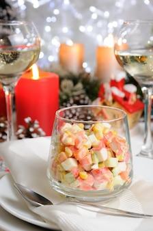 Salada de cubos de carne de caranguejo e vegetais temperada com iogurte em um copo na mesa de natal