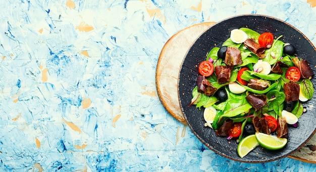 Salada de dieta de acelga, ovos de codorna, tomate e carne seca. salada com jamon e legumes. copie o espaço