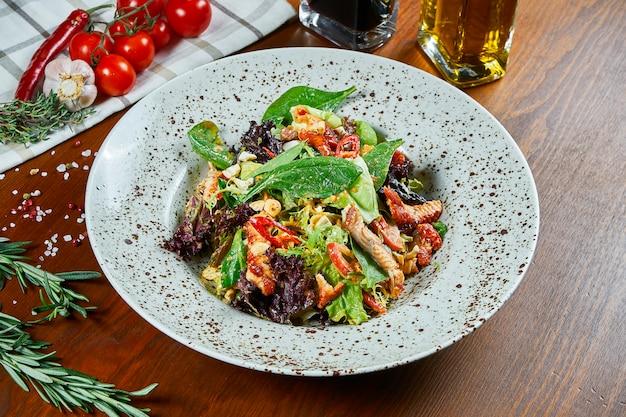 Salada de enguia saborosa em molho teriyaki com espinafre, pimenta e alface em uma tigela branca sobre uma mesa de madeira. salada de frutos do mar. comida deliciosa e saudável. fechar-se