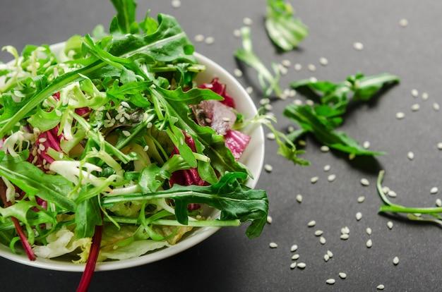 Salada de ervas frescas, rúcula, alface, sal, gergelim em tigela branca sobre fundo preto.