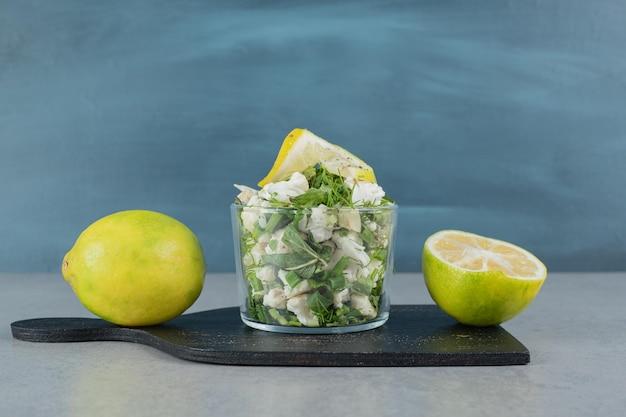 Salada de ervas verde em um copo na mesa de concreto.