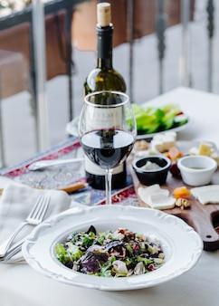 Salada de ervas verdes com um copo de vinho tinto.